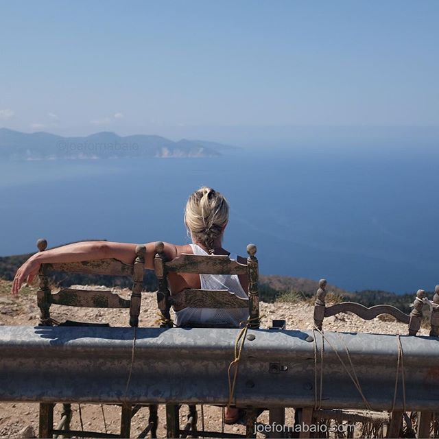 Chairs tied to a steep mountain guard rail with a view.View of Assos.#vacation #joefornabaio #assos #kefalonia #view #greece
